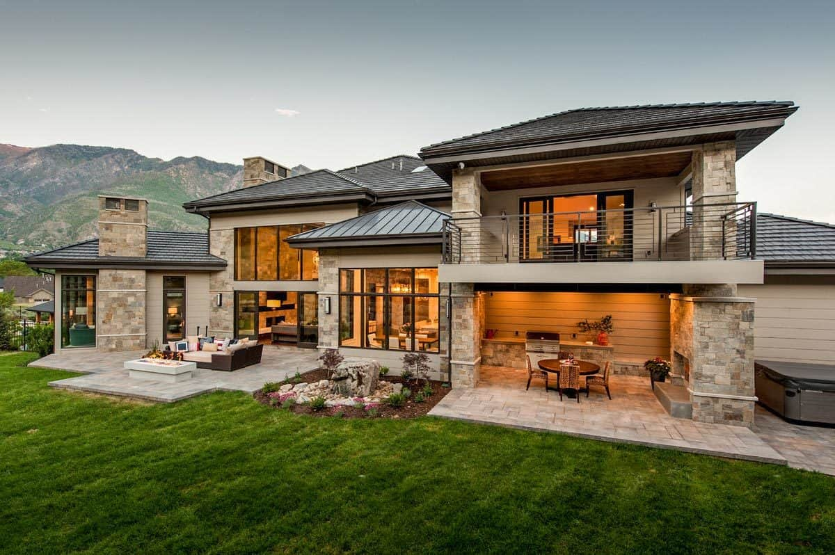Rear exterior view with covered porch, open patio, and a magnificent mountain backdrop.