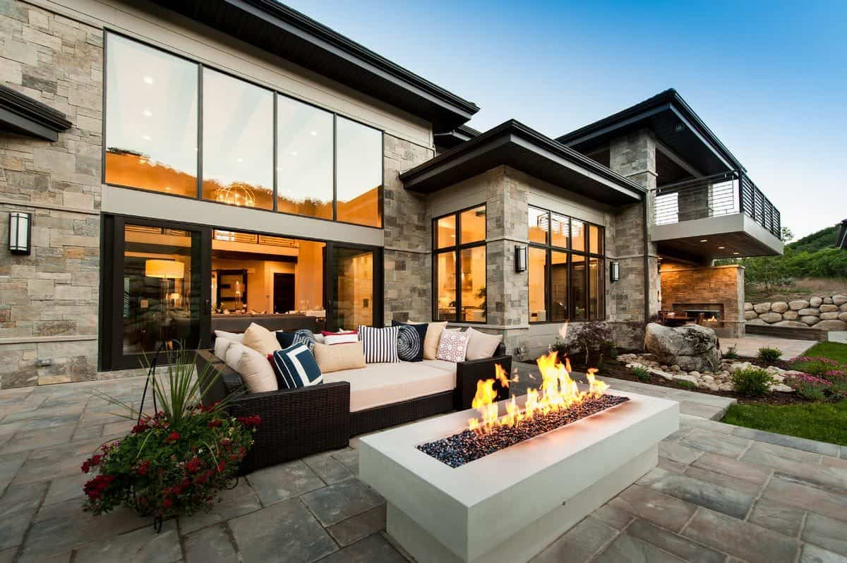 The open patio has a rectangular fire pit table and a large wicker seat filled with striped and eathy pillows.