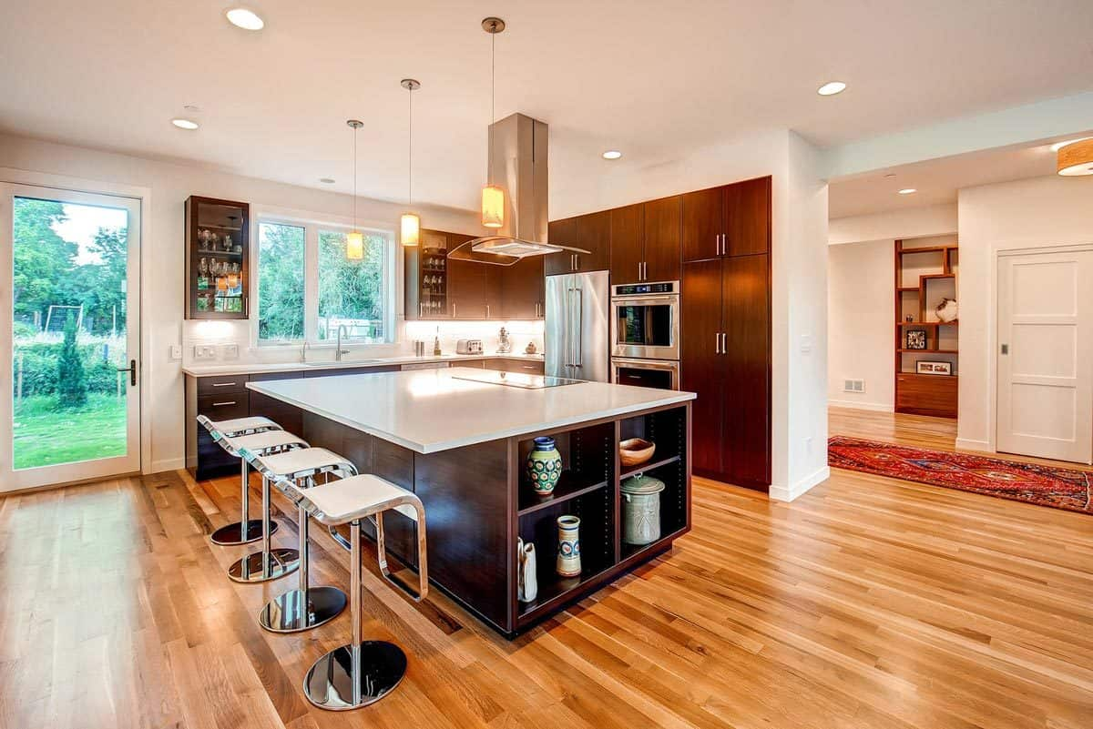 The kitchen is equipped with stainless steel appliances, marble countertops, dark wood cabinetry, and an immense breakfast island.
