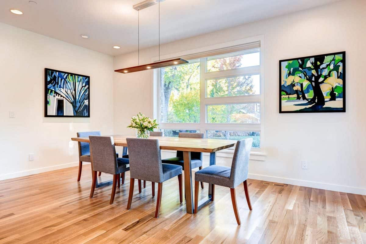 The dining area offers a linear pendant, rectangular dining table, gray upholstered chairs, and bold paintings adorning the white walls.
