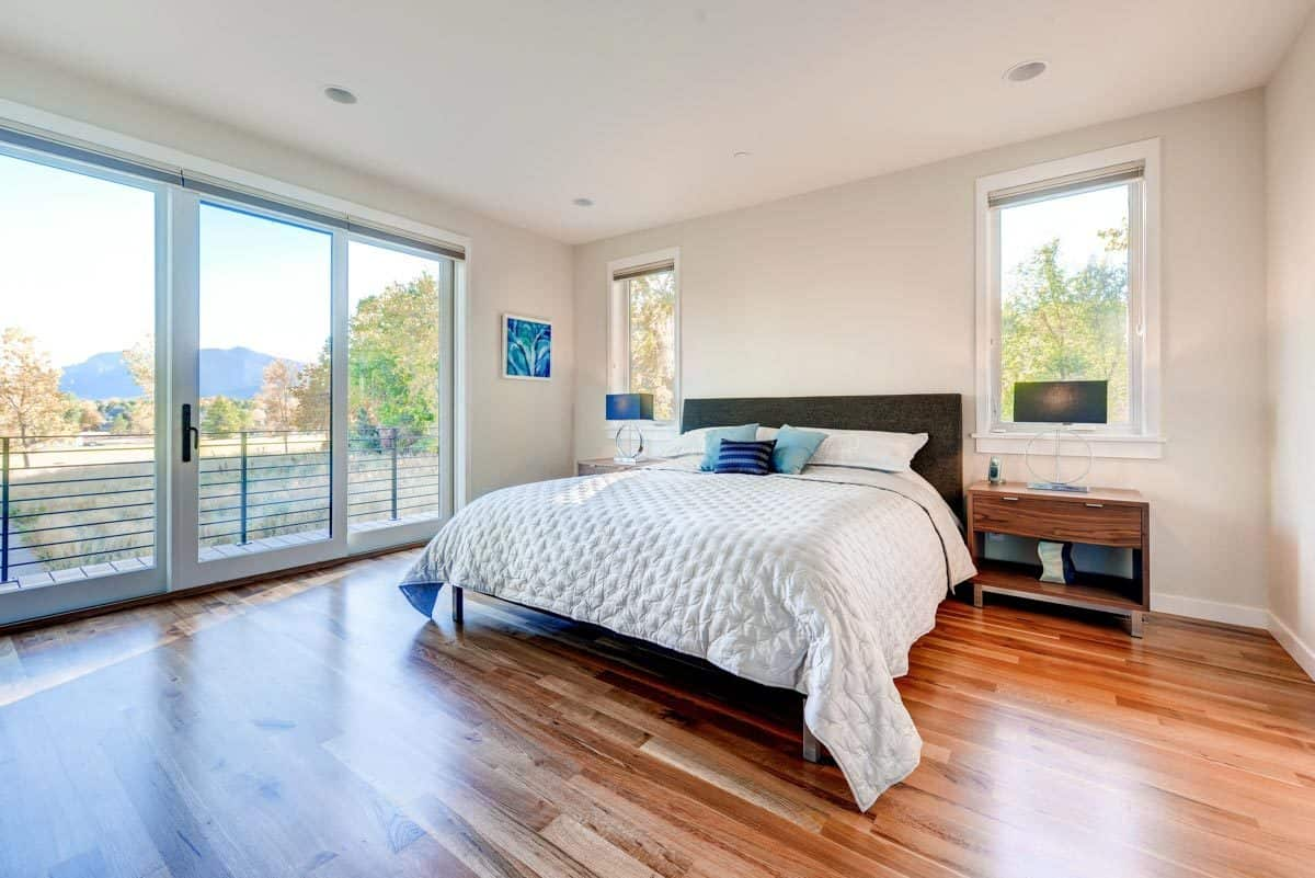 The primary bedroom has wooden furnishings, picture windows, and a glass door that opens to the balcony.