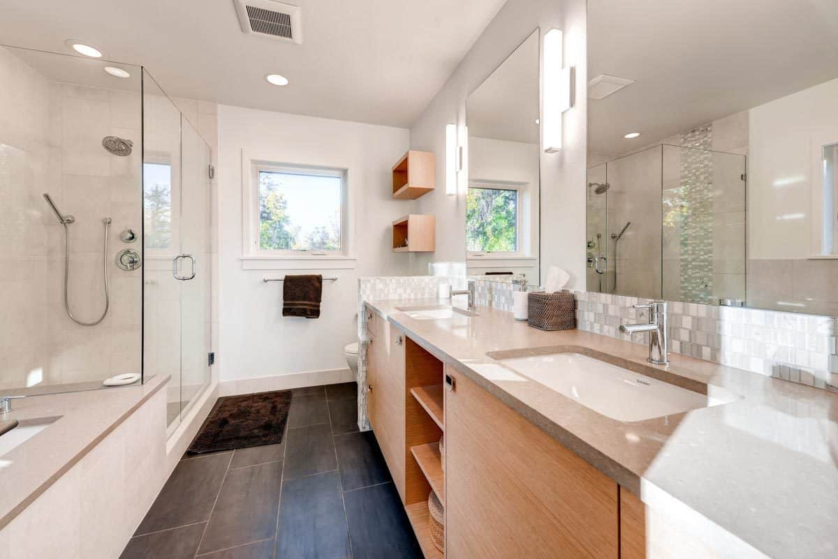 Primary bathroom with a walk-in shower, a deep soaking tub, and a toilet concealed by the dual sink vanity.