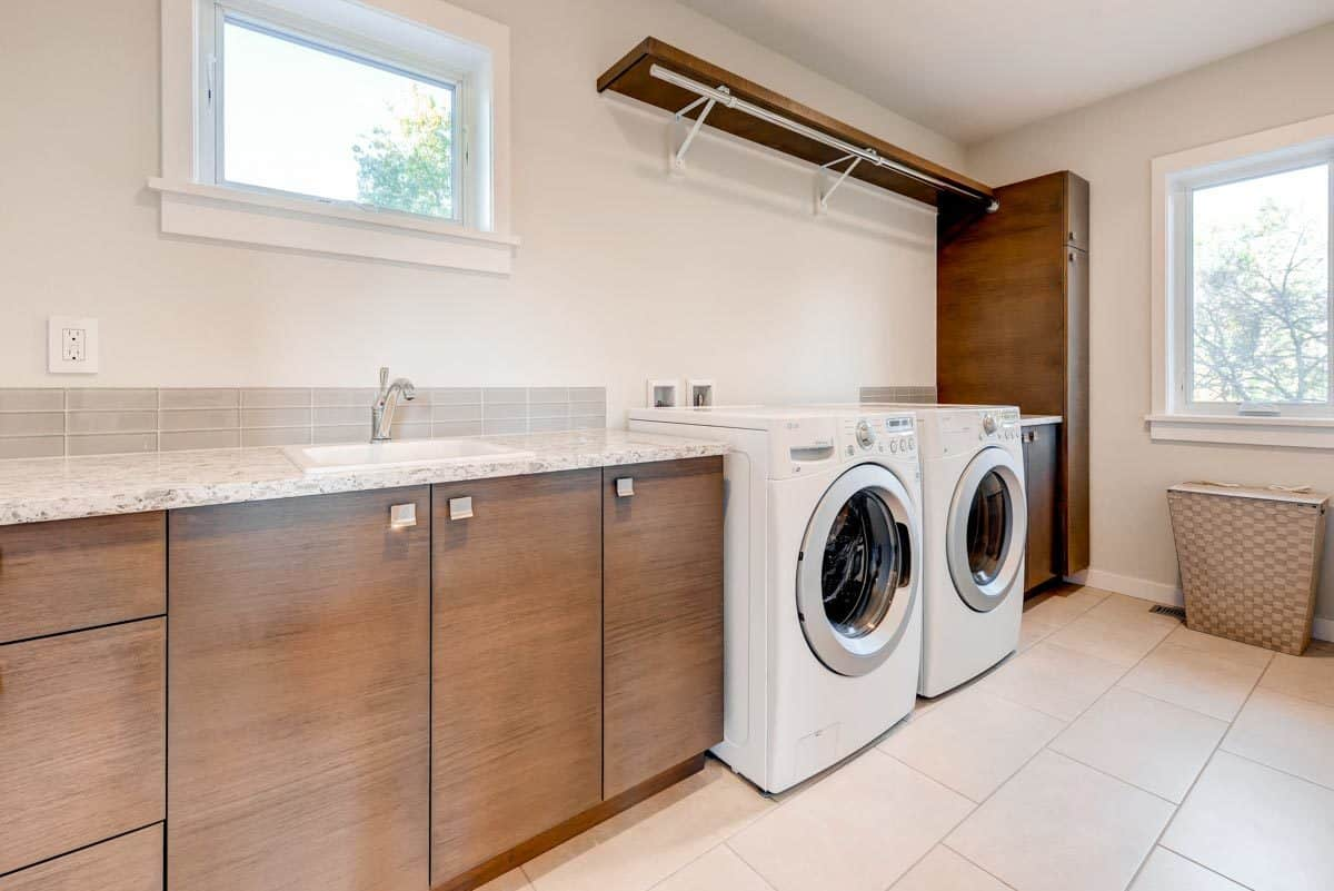 The laundry room is equipped with white front-load appliances, wooden cabinets, and a porcelain sink.