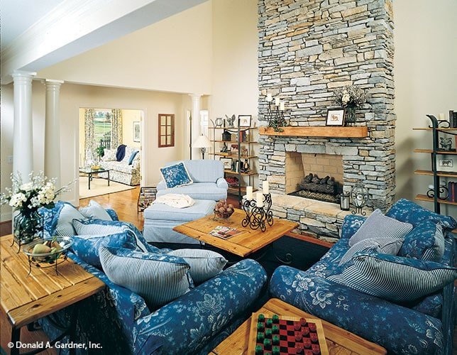 Blue floral chairs, wooden tables, and a stone fireplace complete the family room.