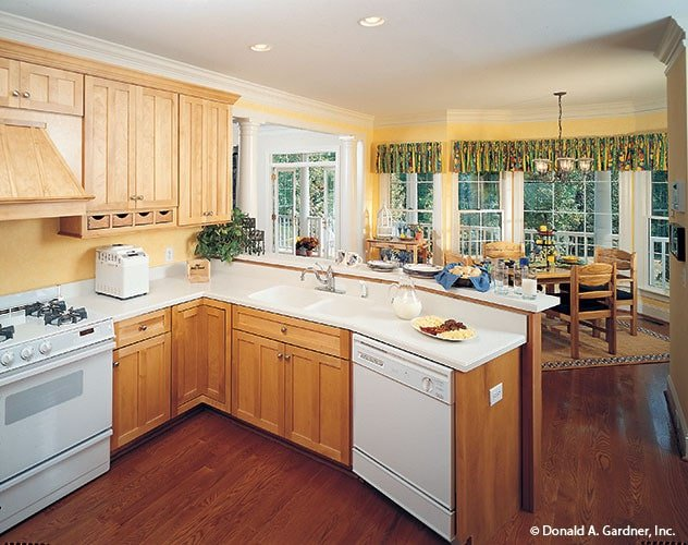 Eat-in kitchen with white appliances, wooden cabinets, quartz countertops, and a two-tier peninsula.
