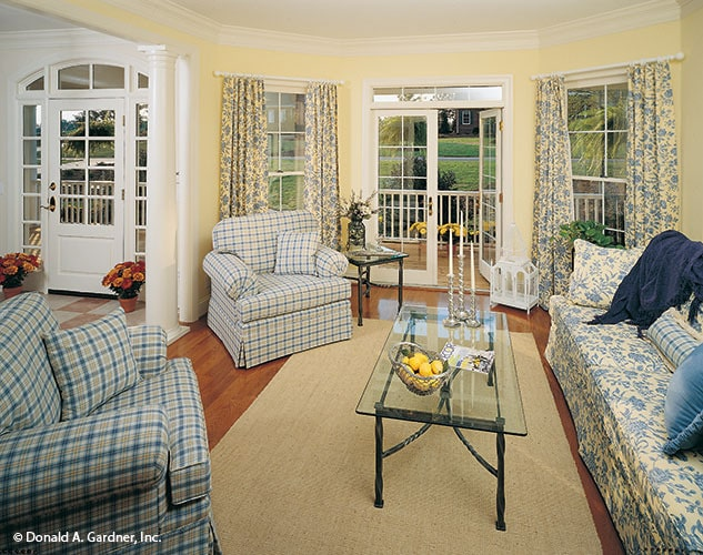 The living room has checkered armchairs, a floral sofa, glass top tables, and a french door that leads out to the covered porch.