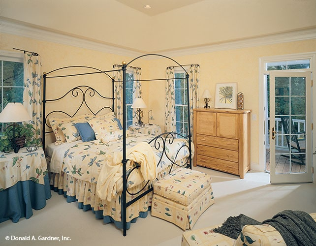 Primary bedroom with an ornate canopy bed, skirted sits, wooden table, and back porch access.