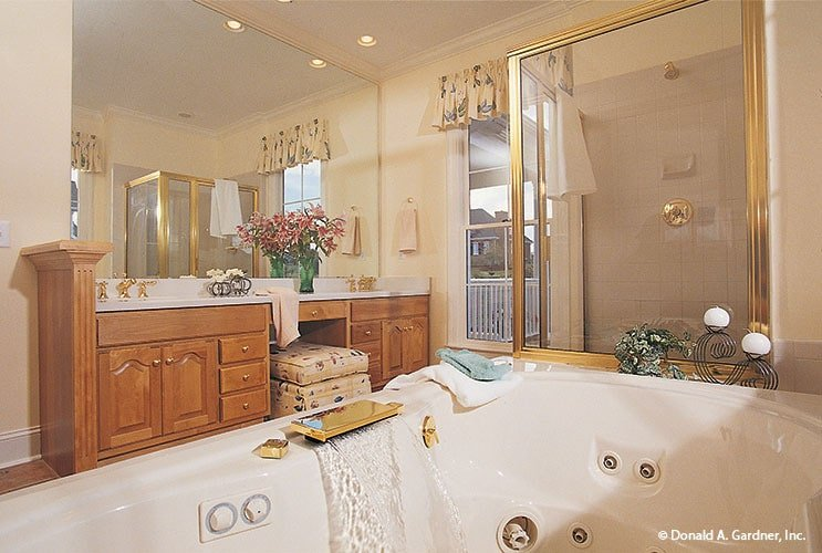 The primary bathroom is equipped with wooden vanity, deep soaking tub, and walk-in shower that's accented with brass trims.