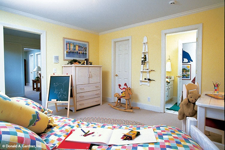 This bedroom has carpet flooring, a colorful bed, a wooden desk, and yellow walls adorned with various wall arts.