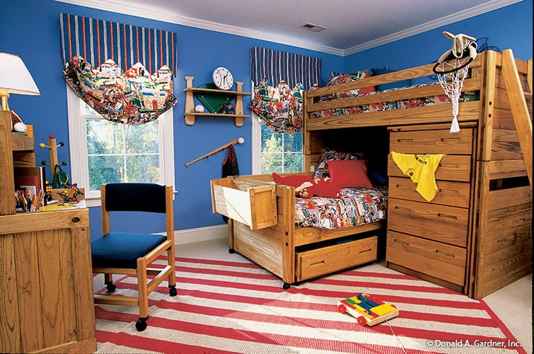 Another bedroom with blue walls, a custom bunk bed, a wood plank desk, and white framed windows dressed in striped shades.