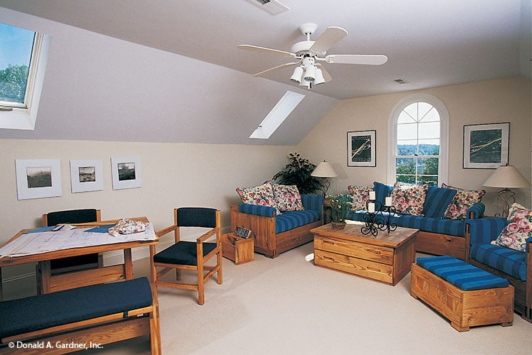 Bonus room with vaulted ceiling, cushioned seats, and an arched window that invites natural light in.