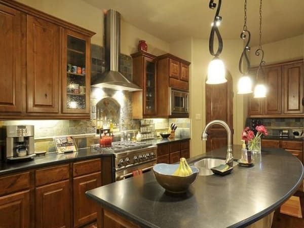 The kitchen has wooden cabinetry, stainless steel appliances, and an arched island fitted with a double bowl sink.