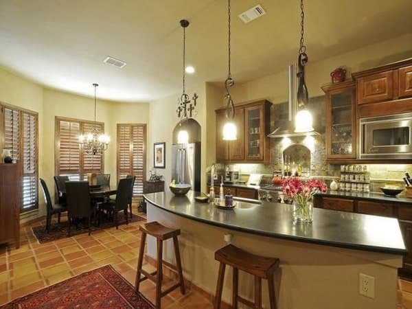Across the kitchen is the breakfast nook with a dark wood dining table placed against the bay window.