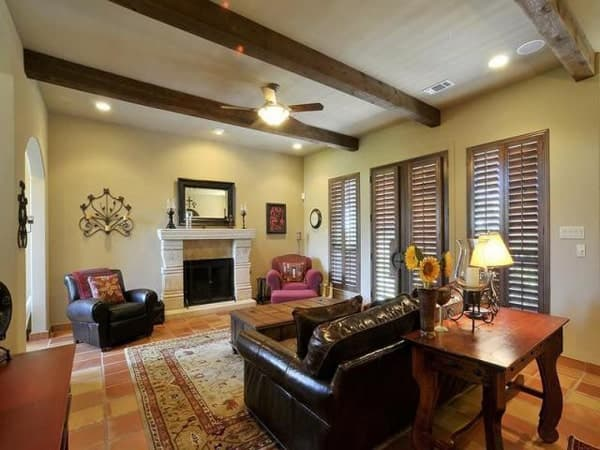 Living room with beamed ceiling, black leather seats, a fireplace, wooden table, and louvered windows.