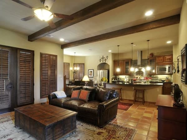 An open layout view showing the living room, kitchen, and breakfast nook well-lit by warm glass pendants and recessed ceiling lights.