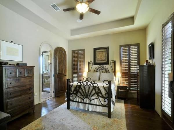 The primary bedroom has an ornate bed, a tray ceiling, dark wood cabinets, and a floral rig that lays on the hardwood flooring.