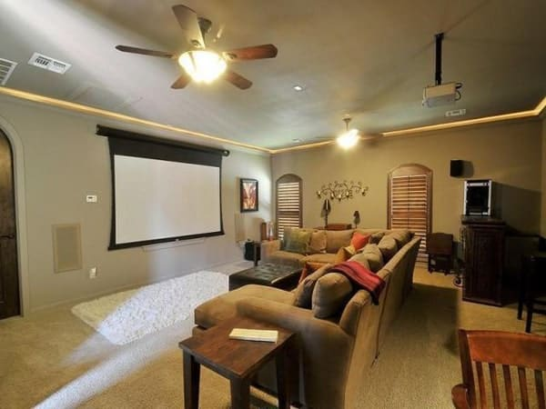 Media room with carpet flooring, a gray velvet sectional, ceiling fans, arched windows, and a projector screen.