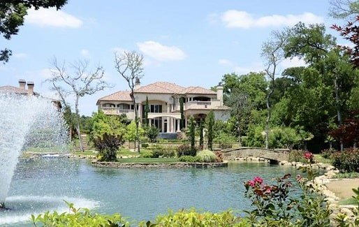 View of the house from the backyard showing the verdant landscaping and man-made lagoon.