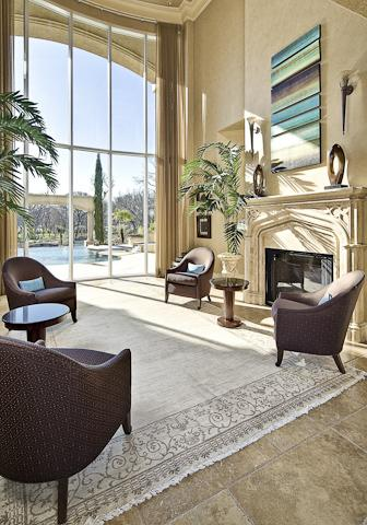 The living room has a marble fireplace, round back chairs, and floor-to-ceiling windows overlooking the pool area.