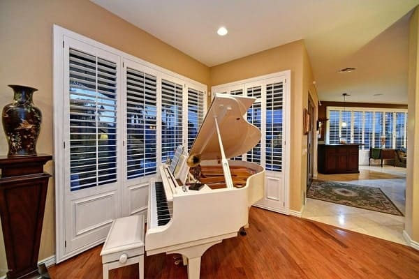 Music area with a white baby grand piano and a wooden pedestal topped with an antique vase.