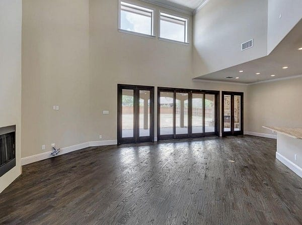 Breakfast area with dark hardwood flooring and glass windows that lead out to the outdoor living.
