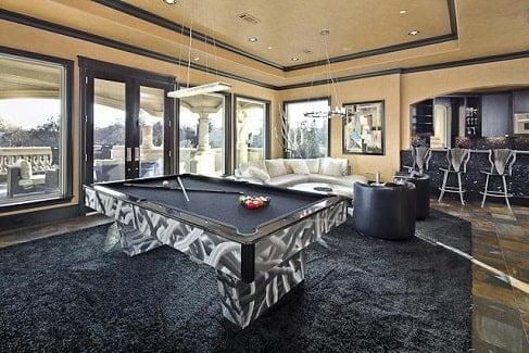 The game room has an L-shaped sectional, leather round back chairs, a wet bar, and a patterned billiard table.