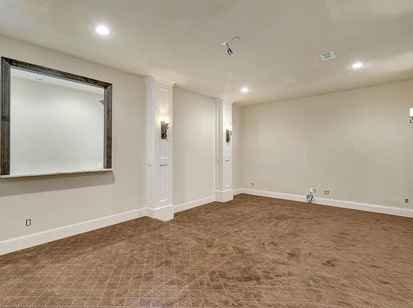 Media room with velvet carpet flooring, white walls, and regular ceiling fitted with recessed lights.