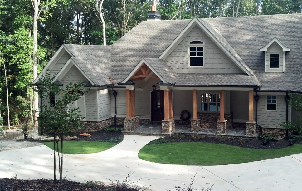 Alternate front exterior with neutral shakes, multiple gables, and tapered columns.