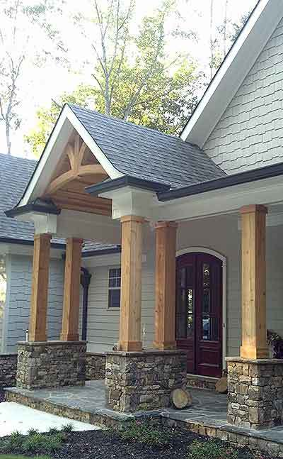 Covered front porch with flagstone flooring, double columns, and a french entry door.