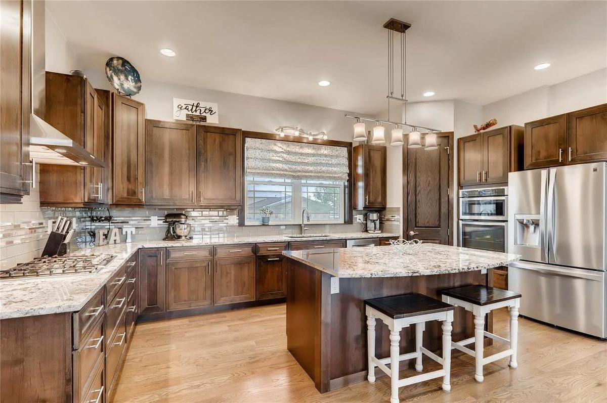 The kitchen is equipped with granite countertops, stainless steel appliances, wooden cabinetry, and a breakfast island.