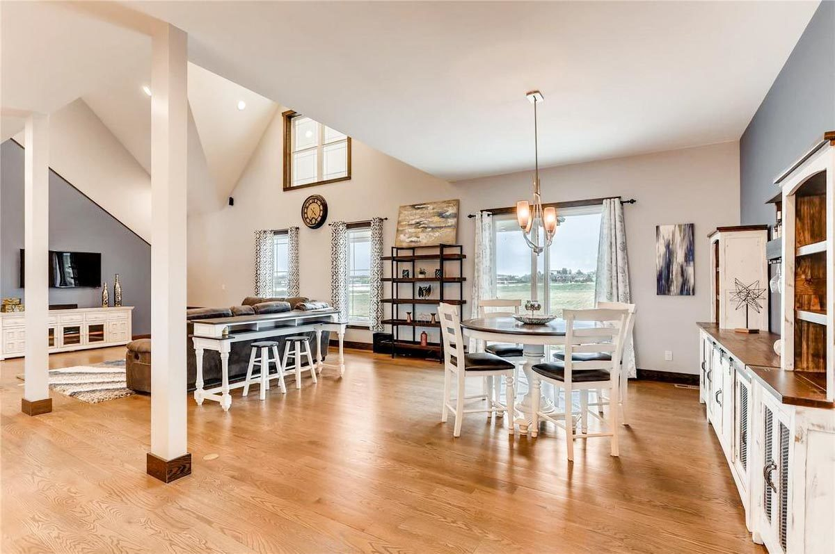 Shared dining and living space with hardwood flooring, vaulted ceiling, and plenty of glazed windows.
