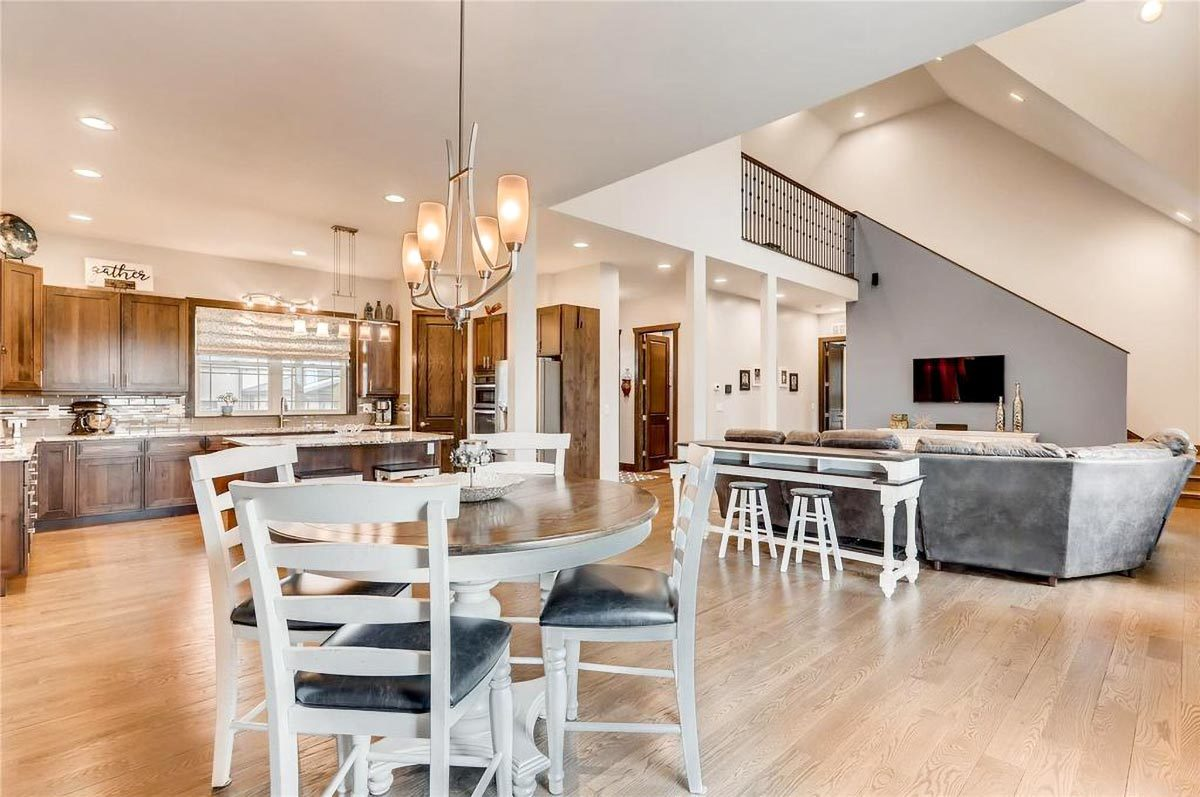 An open layout view showing the dining area, living room, kitchen, and foyer.