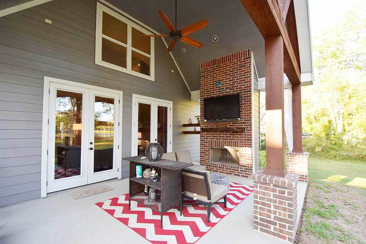 Outdoor living with beige cushioned seats, wooden table, and a brick fireplace topped by a wall-mounted TV.