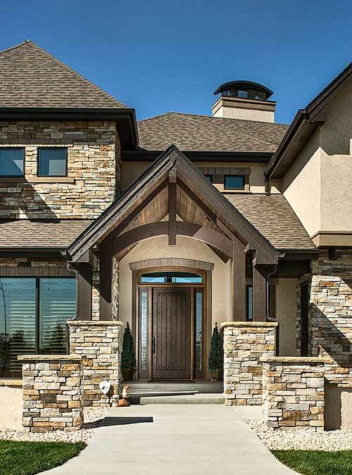Home entry with a wooden front door and an arched covered porch adorned with stone columns.