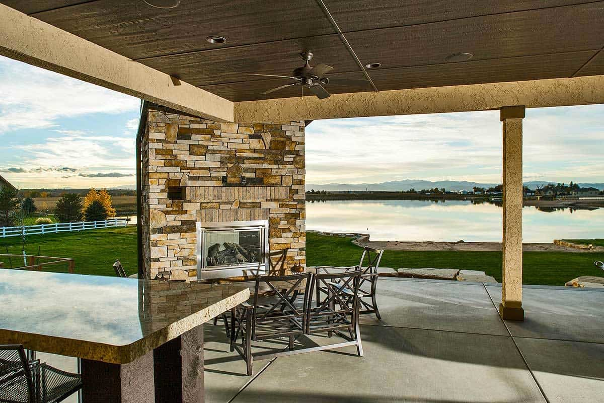 Rear patio with outdoor dining and a corner stone fireplace.