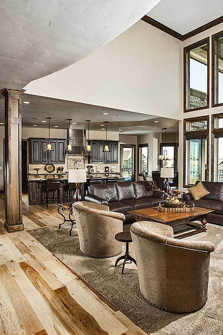 Living room with clerestory windows, leather sectionals, round back chairs, and a wooden coffee table.