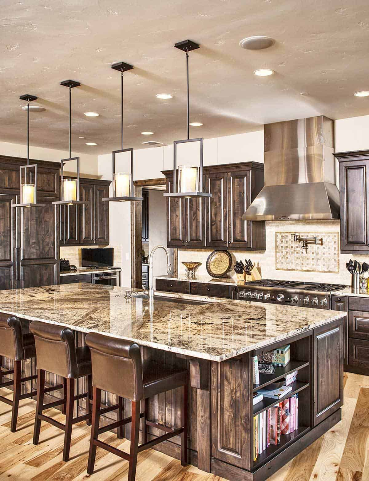 The kitchen is equipped with natural wood cabinetry, stainless steel appliances, granite countertops, and a large breakfast island.