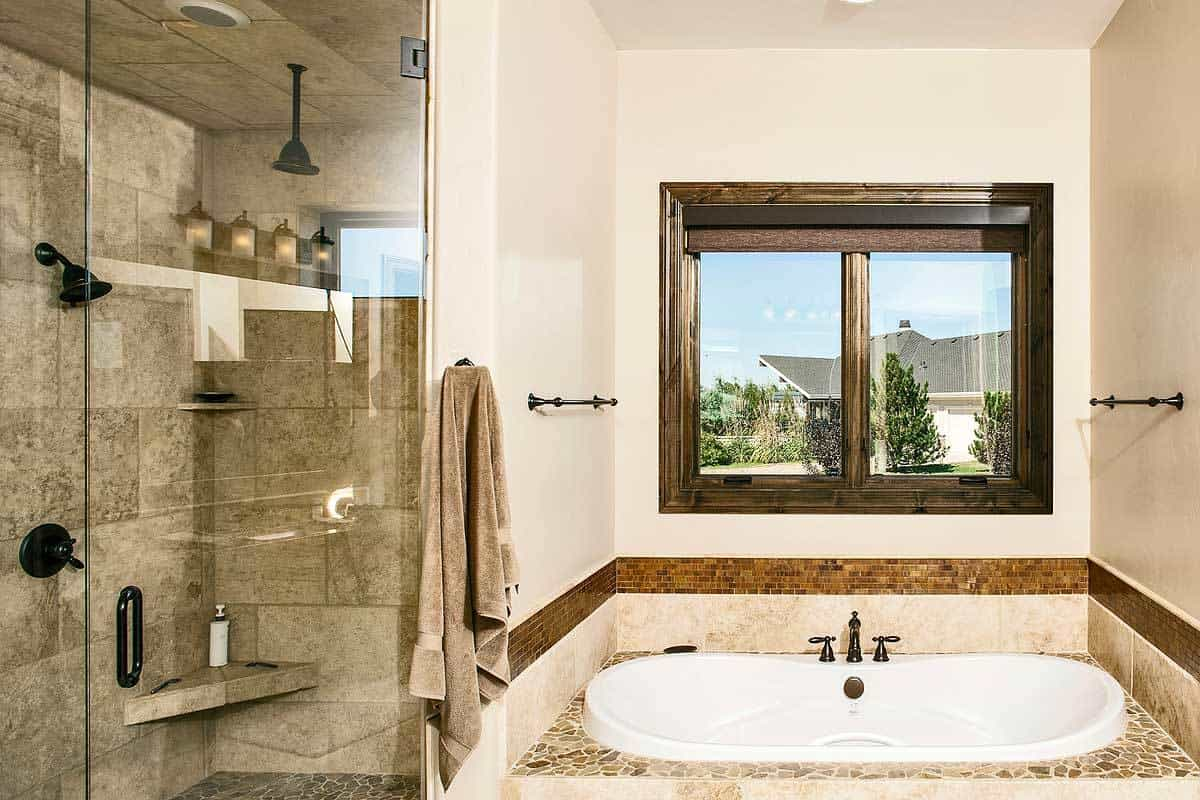 Drop-in bathtub and walk-in shower with wrought iron fixtures complete the primary bathroom.
