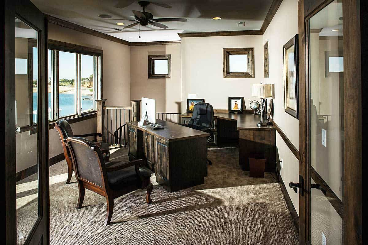 Home office with dark wood desks and leather chairs over carpet flooring.