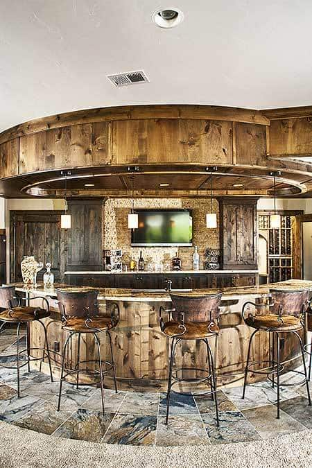 A closer look at the wet bar showing its wooden cabinets, wall-mounted TV, and a curved peninsula paired with ornate metal counter chairs.