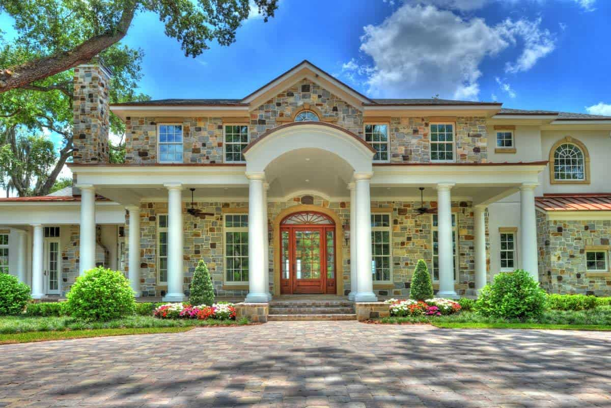 Home entry with an arched front door and a covered porch bordered by decorative columns.