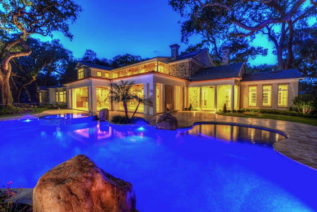 The home's rear view during night shows the stunning pool lights that contrasts the cozy ambient lighting of the house.
