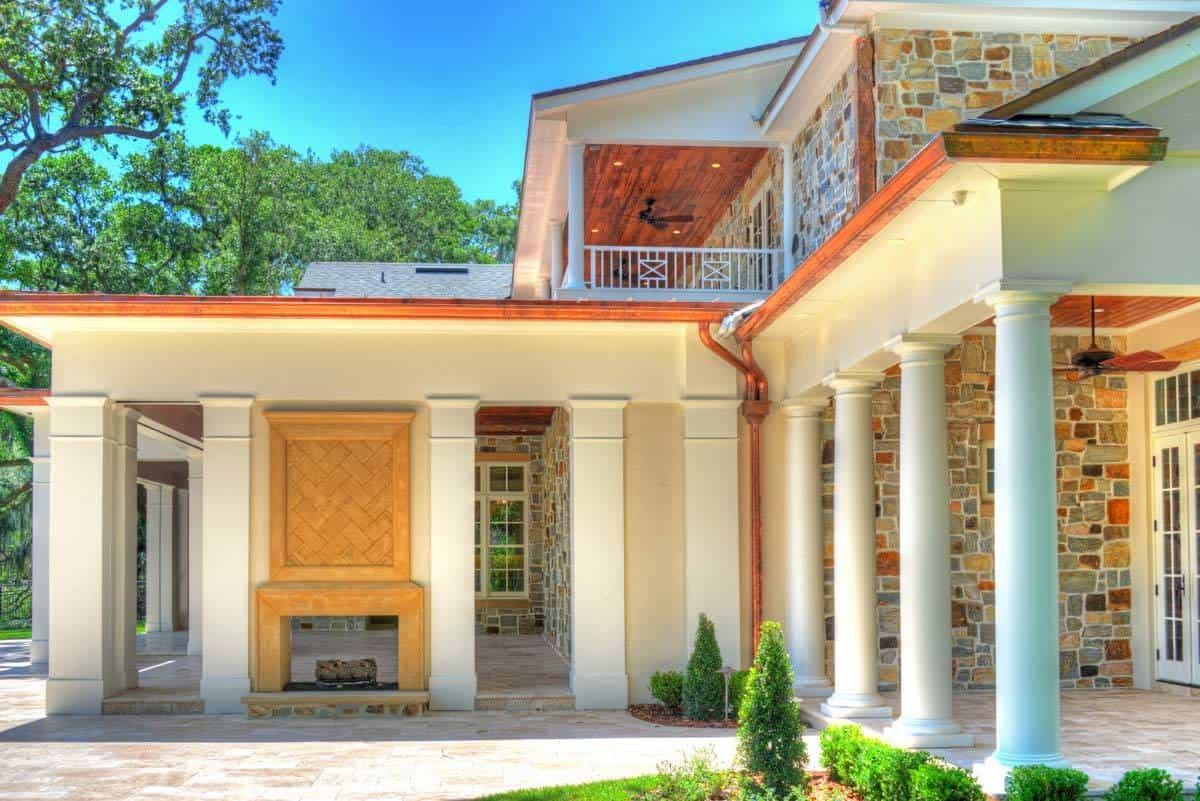 Rear patio with an outdoor fireplace and a covered porch lined by large columns.