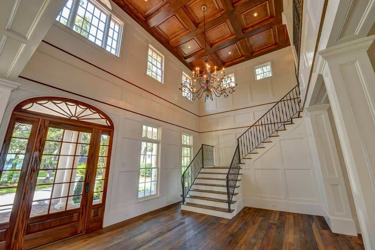 Spacious foyer with a glazed entry door, a grand chandelier, and a traditional staircase.
