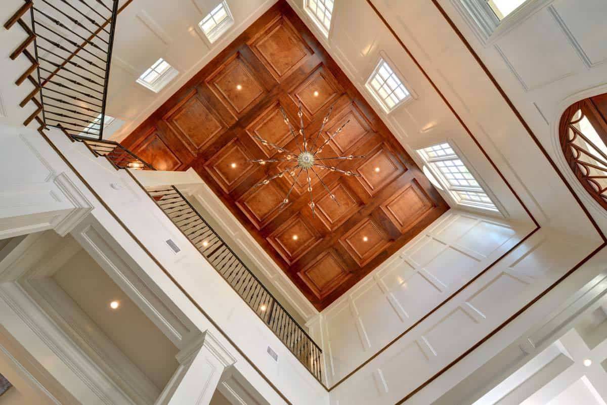 Wooden coffered ceiling mounted with recessed lights and chandelier tops the foyer.