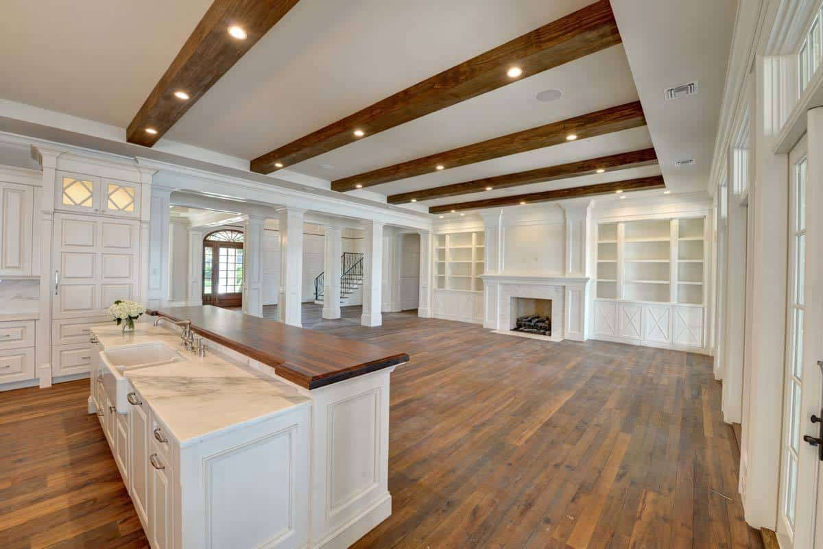 Shared kitchen and living room with a beamed ceiling and a fireplace flanked by white built-ins.