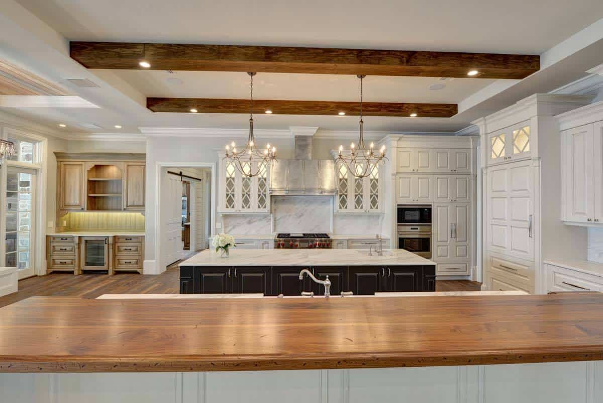 The kitchen is equipped with marble countertops, two islands, white cabinetry, and a butler's pantry.