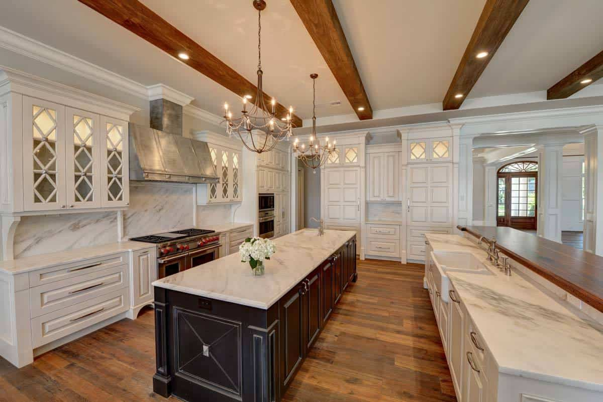 A pair of candle chandeliers along with recessed ceiling lights fitted on the beamed ceiling illuminate the kitchen.