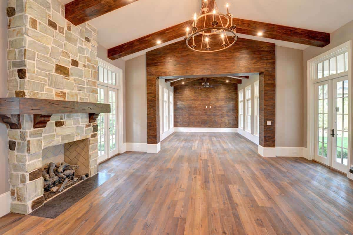This room has a stone fireplace and a vaulted ceiling with exposed rustic beams.