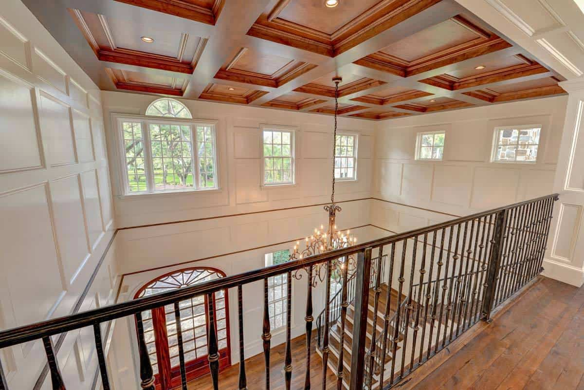 Second-floor balcony with ornate wrought iron railings overlooking the foyer below.